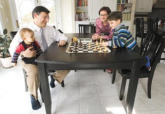 Herald & Review/Kelly J. Huff Home for lunch with his family, Decatur Memorial Hospital's interventional cardiologist Dr. Tansel Turgut plays his sone Aydin in a gmae of chess, while holding his infant son Kaya. His wife Eva looks on wondering who will win their current match.